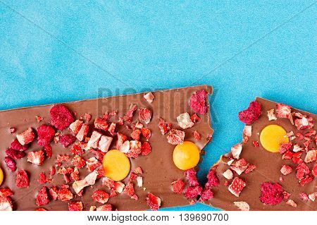 Top view of an orange strawberry and raspberry milk chocolate tablet broken in two pieces on a cyan background.