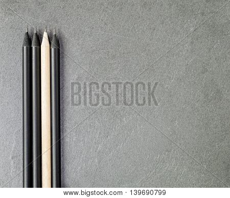 Light colored pencil among three black ones on a gray granite slate.