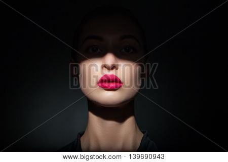 Portrait of beautiful woman with bright lips and half face covered in shadow