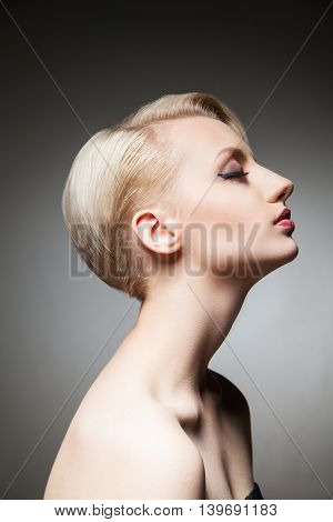 Side view of sensual and dreaming blonde model with hairstyle and make-up with eyes closed.Studio shot.