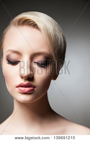 Close-up of young model with make-up, smooth skin and short blonde hair looking down.Studio shot.