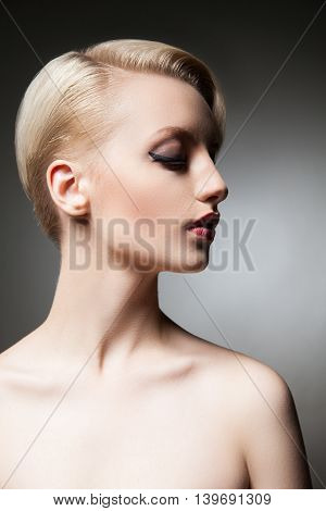 Half face of calm young model with short blonde hair and make-up with bare shoulders looking down.Studio shot.