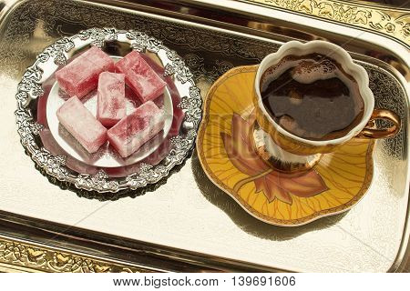 Black coffee and Turkish deligh on plate