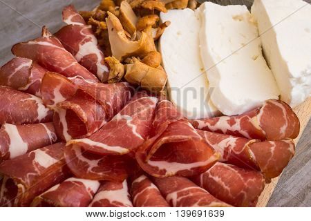 White cheese, mushrooms and prosciutto on wooden background