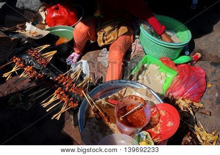 BALI, INDONESIA - 24 JULY: A female Balinese-Hindu street-food seller prepares pork sate kebab snacks and spicy sambal sauce for passers-by at a street stall on 24 July, 2016 in Bali, Indonesia.
