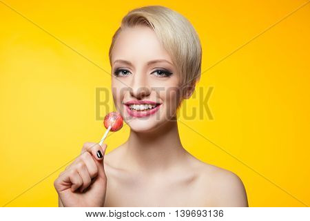 Portrait of pretty smiling blondie with bright lollipop on yellow background