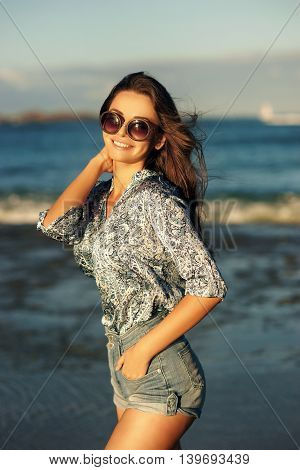 Young, beautiful girl walking at the beach at sunset. Stylish woman with long hair standing in blouse and jeans shorts
