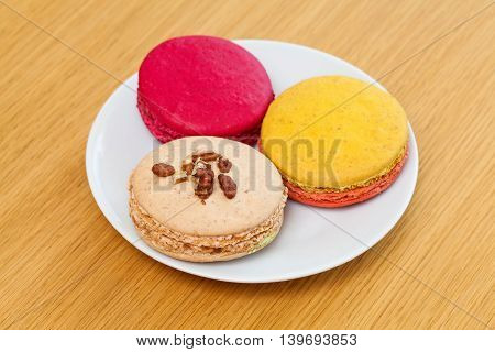 Three Traditional French Colorful Macarons On Plate, Wooden Background