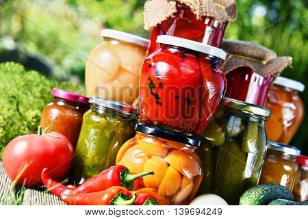 Jars Of Pickled Vegetables And Fruits In The Garden