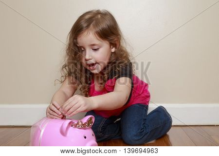 little girl excited to put money in her piggy bank