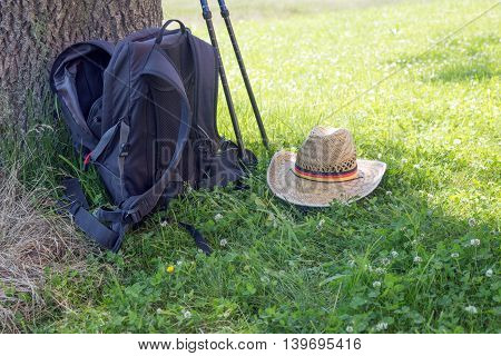 Backpack, hiking poles and hat in the meadow