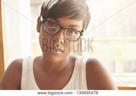 Portrait Of Serious Confident African Female Freelancer Wearing Glasses Looking At The Camera With T