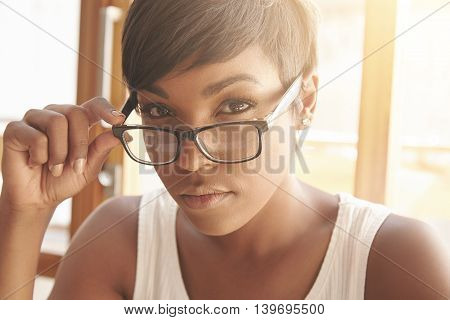 Close Up Portrait Of Beautiful Dark-skinned Female Student With Short Haircut Touching Her Spectacle