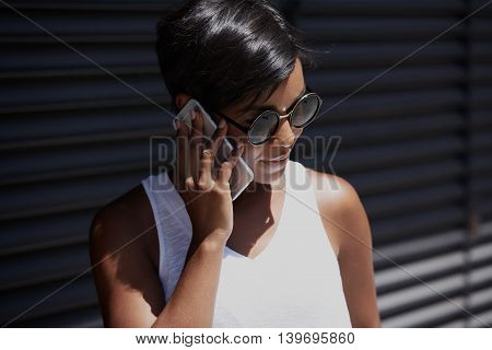 Half Profile Of Successful And Confident Dark-skinned Businesswoman In Round Stylish Sunglasses And