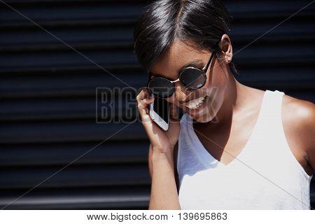 Stylish Beautiful Dark-skinned Businesswoman Wearing White Top And Trendy Shades, Walking Along The