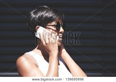 Portrait Of Smiling Good-looking African Female In Round Hipster Sunglasses Looking Puzzled And Conf