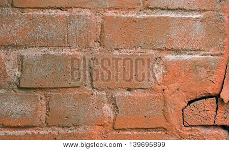Old brick wall with signs of paint and cracks