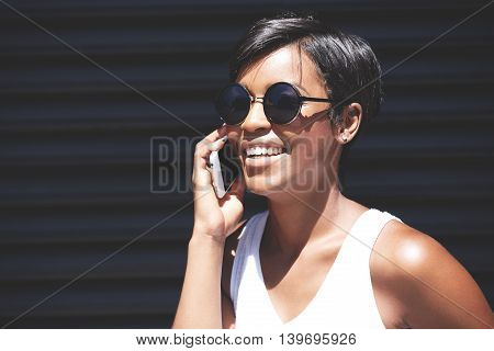 Close Up Portrait Of Dark Skinned Female Laughing At A Joke While Talking On Smart Phone To Her Sist