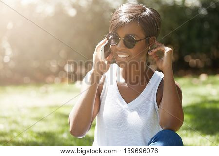 Headshot Of Stylish Young Woman With Short Pixie Haircut Wearing Round Shades Making Phone Calls, Sm