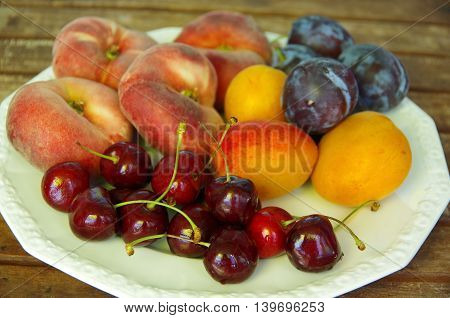 Different fruits on a plate, flat peaches, apricots, plums and cherries