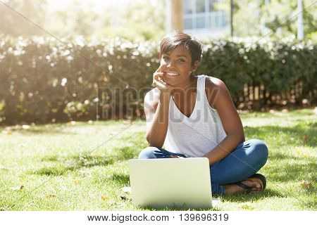 Happy Young Black Female Traveller, Sitting On The Grass, Chatting With Her Family Using Laptop, Smi