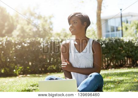 Outdoor Portrait Of Young Charming African American Woman, Sitting On The Grass At A Park With Her L