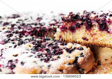 home-made cake with blueberries and powdered sugar on wooden table