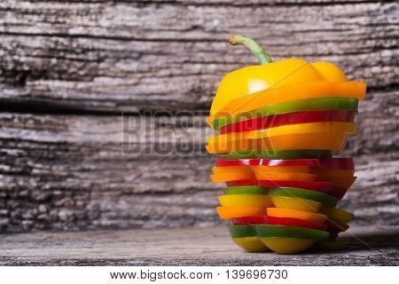 Orange red yellow and green paprika peppers with slice over wooden table
