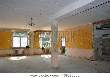 The process of repair reconstruction of the building. Peeled yellow walls and columns and gray concrete floor.