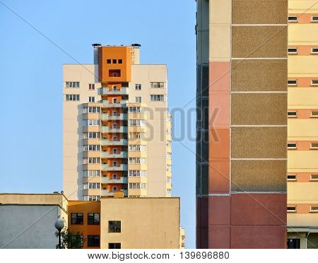 Modern residential district. Fragments of panel multistory building and high-rise residential house in the distance. Geometrical composition.