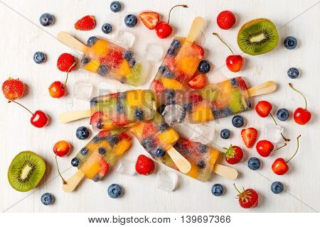 Homemade popsicles with berries and fruits top view.