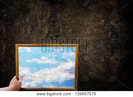 Hand Hold Picture Frame Of Wide Puffy Cloud Sky On Dark Grunge Wall