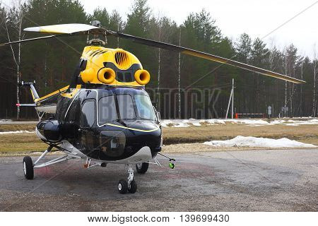 Aircraft - Big black-yellow helicopter on the parking against the wood.