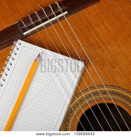 Musical instruments - the Acoustic guitar and a notebook with a pencil.