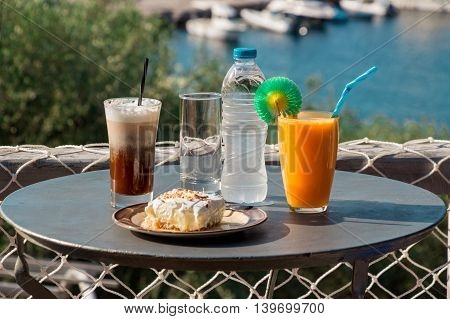 Coffee, orange juice, cheese ham toast, ekmek dessert, water for breakfast near the aegean sea with views of the marina and seascape.