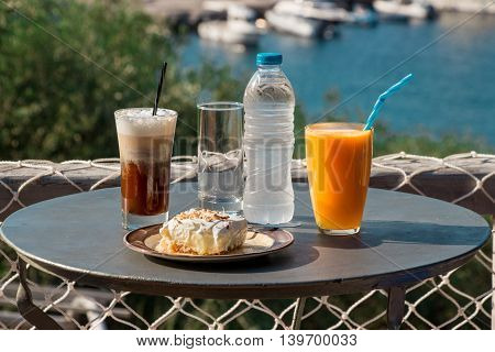 Coffee, orange juice, cheese ham toast, ekmek dessert, water for breakfast the aegean sea with views of the marina and seascape.