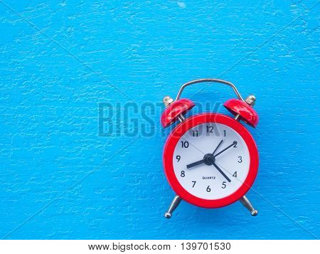 Vintage red clock on wooden background Concept time to wake up