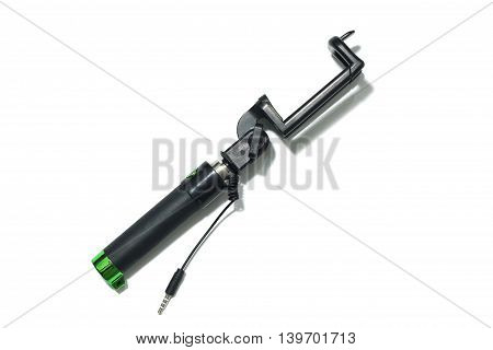 close up top view an extensible selfie stick with an adjustable clamp on the end isolated on white background