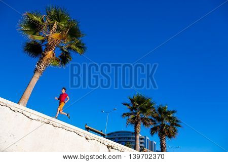 Sporty Man jogging at seafront Promenade Alley at Tropical Town running Palm Tree blue Sky Intentionally Tilted Horizon to add some more action