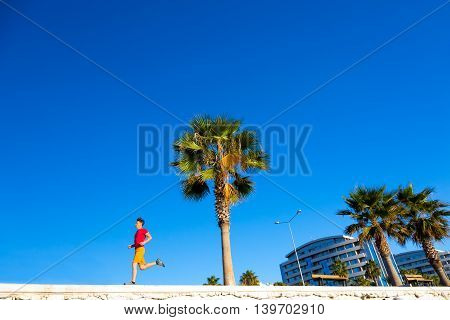 Sporty Man jogging at seafront Promenade Alley at Tropical Town running Palm Tree blue Sky