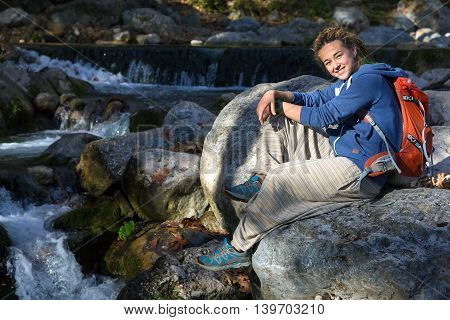 Cute Young Woman sitting on Stone near Mountain Creek Smiling and enjoying warm Sunlight Female Hiker with Backpack and Sporty Clothing