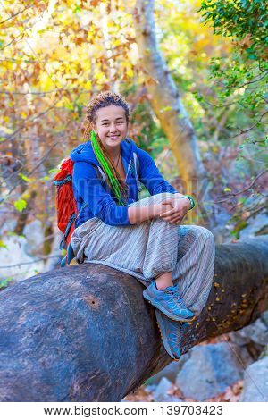 Joyful Girl with Backpack and Hippie style clothing sitting on large trunk of a fallen Tree in Forest with Sun Beams coming throw Autumnal leaves