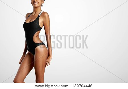 Smiling Woman Wears Black Swimsuit In A Grey Studio