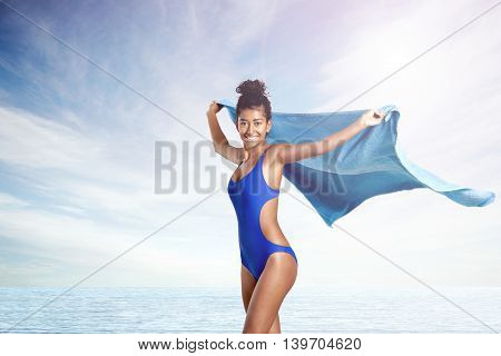 woman on beach with flying towel wears swimsuit