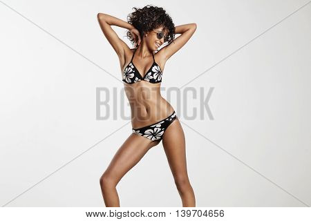 woman in bikini dansing in studio wears glasses