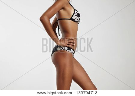 Woman With Ideal Body In Bikini On A Grey Background