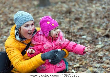 European Family Mother and Little Baby Girl sitting in Autumnal Forest Pointing on something Watching and Looking