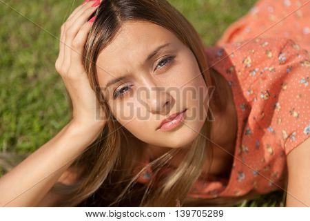 Beautiful girl lying on the grass and smiling while looking at the camera. Horizontal photo