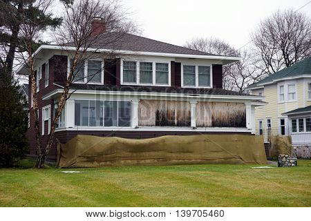 The front porch of a brown home, on Beach Drive in Wequetonsing, Michigan, is boarded up for the winter weather.