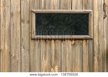 A small closed window in unpainted rustic wooden wall of a wooden house horizontal view